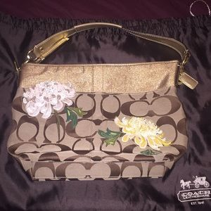 Gold/tan Coach bag with flower accents